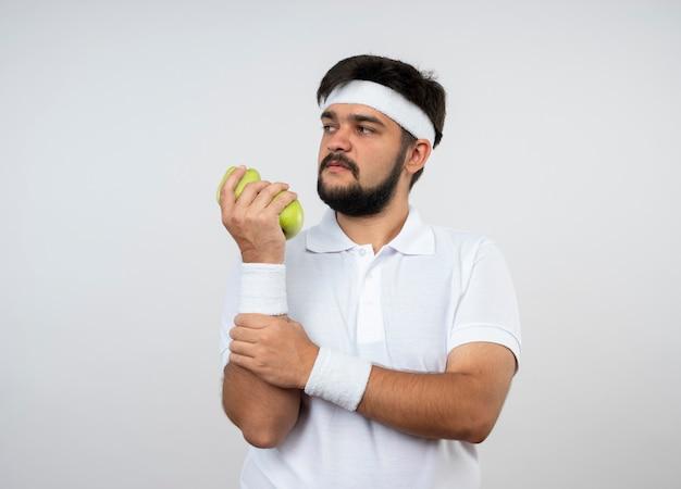 Fiducioso giovane uomo sportivo guardando lato indossando la fascia e il braccialetto che tiene la mela ha afferrato il braccio isolato su bianco con lo spazio della copia
