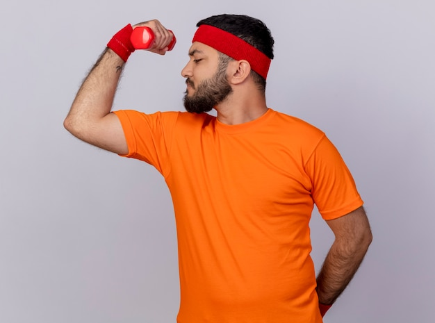 Confident young sporty man standing in profile view wearing headband and wristband exercising with dumbbell isolated on white background
