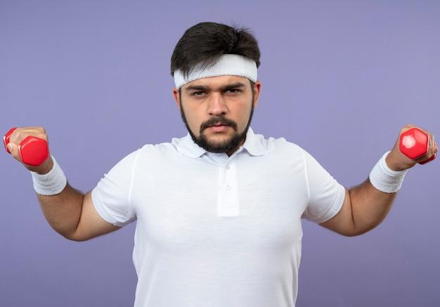 아령으로 운동하는 머리띠와 팔찌를 착용하는 자신감이 젊은 스포티 한 남자