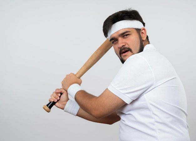 흰 벽에 고립 된 야구 방망이를 들고 머리띠와 팔찌를 착용하는 자신감이 젊은 스포티 한 남자