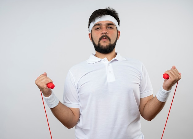 Уверенный молодой спортивный мужчина с повязкой на голову и браслетом, держащим скакалку, изолированную на белой стене