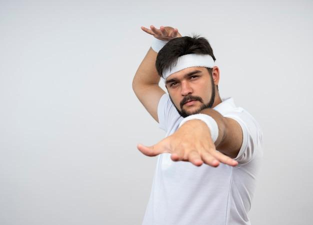 Уверенный молодой спортивный мужчина в повязке на голову и браслет, протягивая руку, изолированную на белой стене с копией пространства