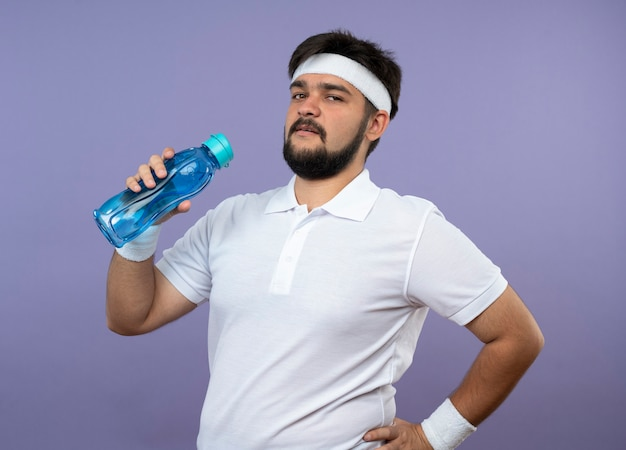 緑で隔離の腰に手を置く水筒を保持しているヘッドバンドとリストバンドを身に着けている自信を持って若いスポーティな男