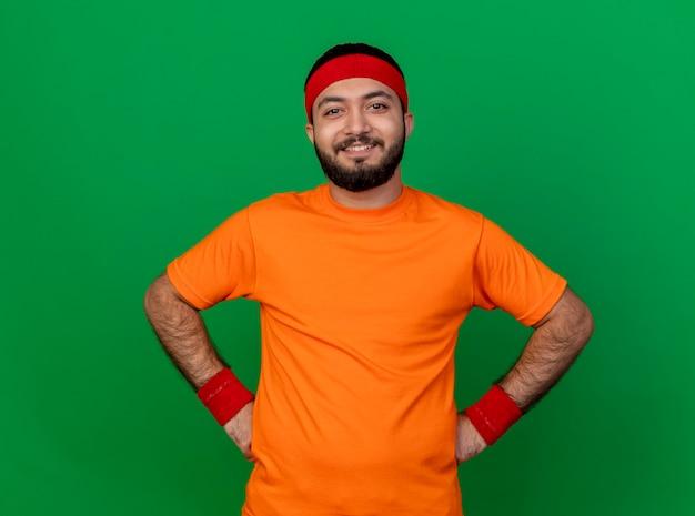 緑の背景で隔離の腰に手を置くヘッドバンドとリストバンドを身に着けている自信を持って若いスポーティな男