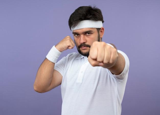 싸우는 포즈에 서있는 머리띠와 팔찌를 착용하는 자신감이 젊은 스포티 한 남자