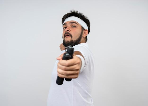 コピースペースで白で隔離の縄跳びを伸ばすヘッドバンドとリストバンドを身に着けている自信を持って若いスポーティな男