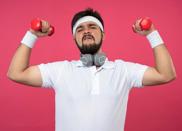 Уверенный молодой спортивный мужчина в головной повязке и браслете с наушниками, упражнениями с гантелями, изолированными на розовом