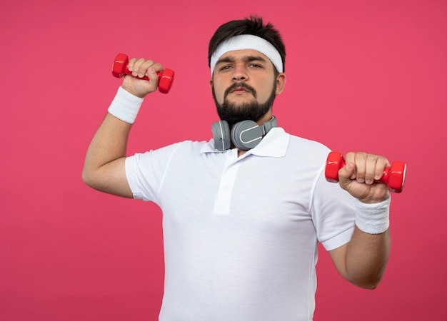 아령으로 운동하는 헤드폰으로 머리띠와 팔찌를 착용하는 자신감이 젊은 스포티 한 남자