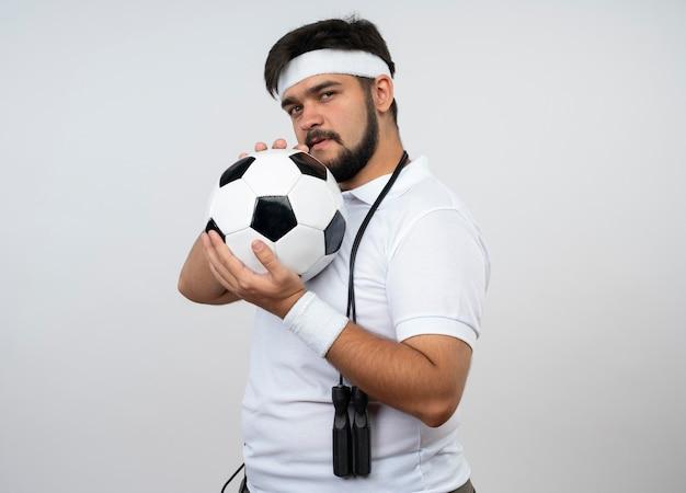 Уверенный молодой спортивный мужчина в повязке на голову и браслет со скакалкой на плече, держащий мяч вокруг лица, изолированного на белой стене с копией пространства