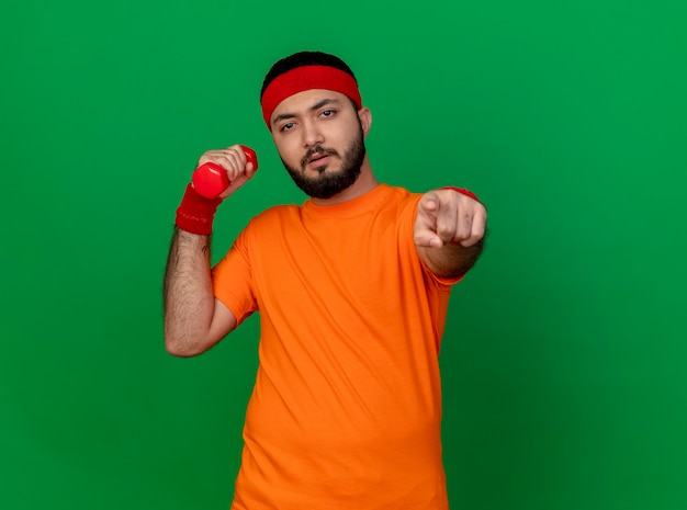 Confident young sporty man wearing headband and wristband exercising with dumbbell showing you gesture isolated on green background