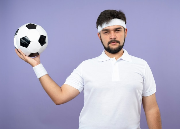 Confident young sporty man wearing headband and wristband holding out ball at side