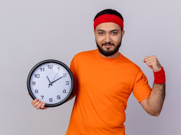 Confident young sporty man wearing headband and wristband holding wall clock showing strong gesture isolated on white background