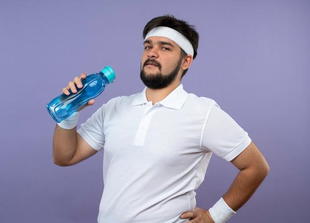 Fiducioso giovane uomo sportivo che indossa la fascia e il braccialetto tenendo la bottiglia d'acqua mettendo la mano sul fianco isolato su verde