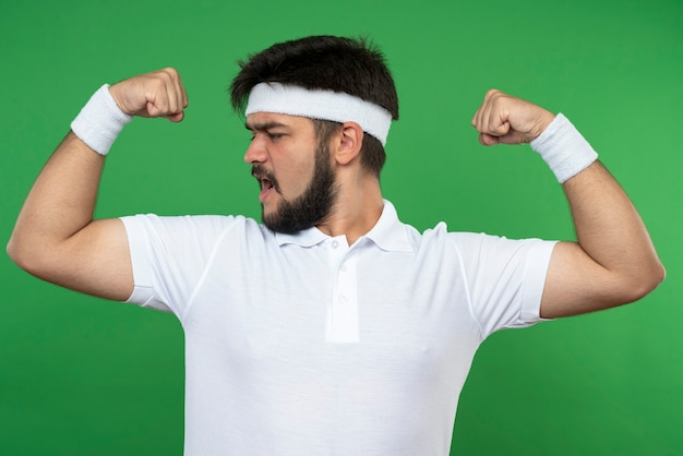 Confident young sporty man wearing headband and wristband showing strong gesture isolated on green