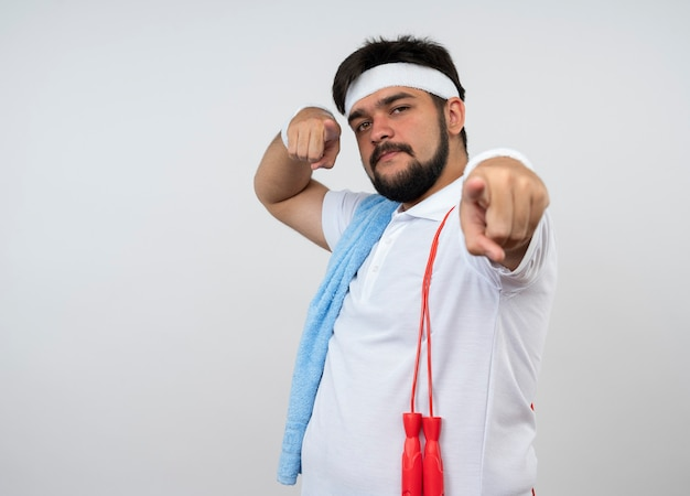 Confident young sporty man wearing headband and wristband with towel and jump rope on shoulder showing you gesture isolated on white wall with copy space