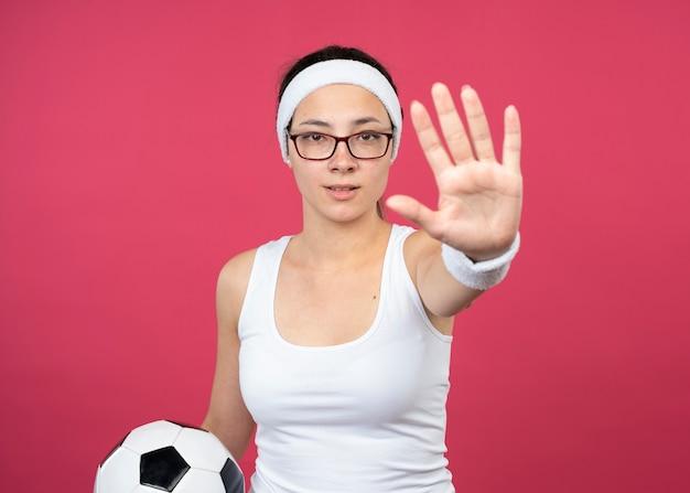 Уверенная молодая спортивная женщина в оптических очках с повязкой на голову и браслетами держит мяч и жестами останавливает знак рукой, изолированную на розовой стене