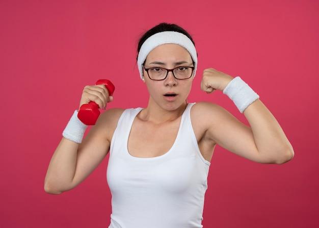 Fiduciosa giovane donna sportiva in occhiali ottici che indossa fascia e braccialetti tiene bicipiti manubri e tempi verbali isolati sulla parete rosa
