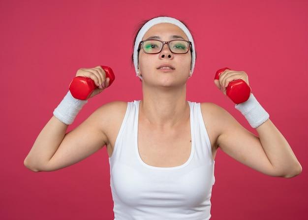 Fiduciosa giovane donna sportiva in occhiali ottici che indossa fascia e braccialetti tiene manubri isolati sulla parete rosa
