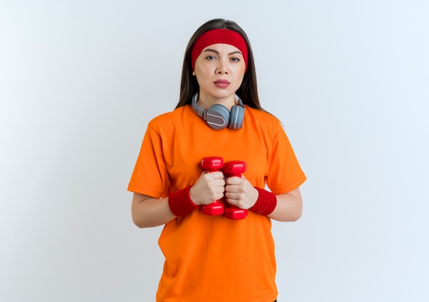 分離されたダンベルを保持しているように見える首にヘッドバンドとリストバンドとヘッドフォンを身に着けている自信を持って若いスポーティな女性