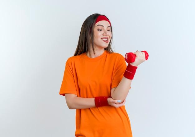 Уверенная молодая спортивная женщина с повязкой на голову и браслетами, держащая и смотрящая на гантель, кусающая губу, касаясь изолированного локтя