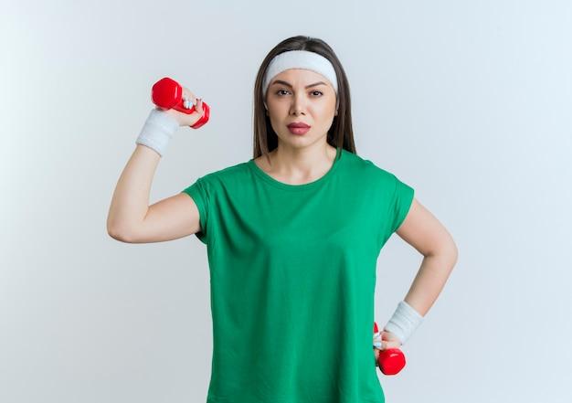 Уверенная молодая спортивная женщина в головной повязке и браслетах с гантелями
