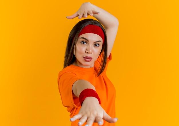 ヘッドバンドとリストバンドを身に着けている自信を持って若いスポーティな女性が手を伸ばして、頭の上に別の手を隔離して見ている