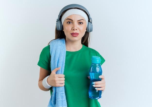 Fiduciosa giovane donna sportiva che indossa la fascia e braccialetti e cuffie con asciugamano sulla spalla tenendo la bottiglia d'acqua afferrando asciugamano alla ricerca