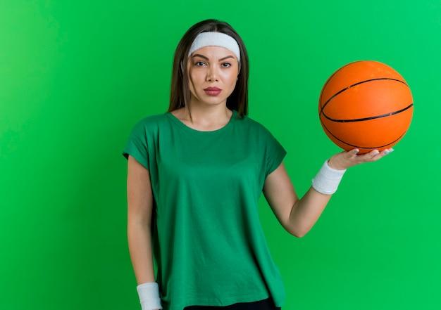 Fiduciosa giovane donna sportiva che indossa la fascia e braccialetti tenendo palla da basket cercando