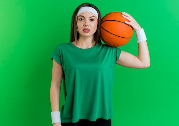 Fiduciosa giovane donna sportiva che indossa la fascia e braccialetti tenendo palla da basket sulla spalla alla ricerca
