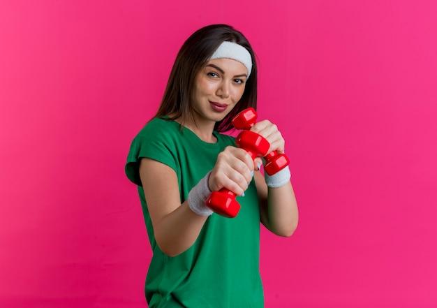 Fiduciosa giovane donna sportiva che indossa la fascia e braccialetti cercando di tenere e allungare i manubri