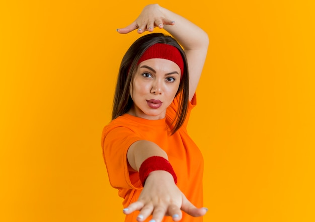 Confident young sporty woman wearing headband and wristbands stretching out hand towards, looking keeping another hand above head isolated