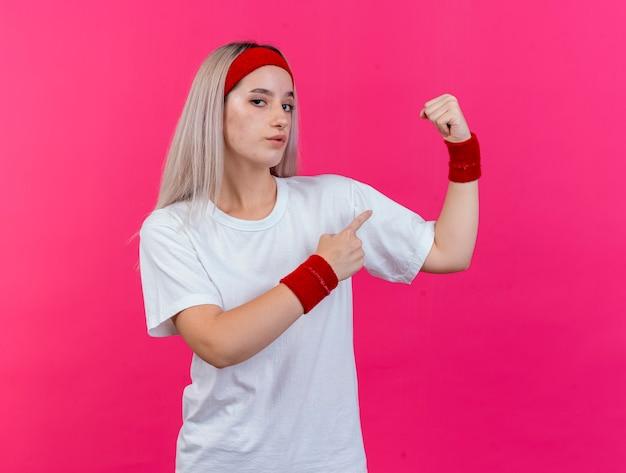ピンクの壁に分離された上腕二頭筋にヘッドバンドとリストバンドの緊張とポイントを身に着けている中かっこを持つ自信を持って若いスポーティな女性 無料写真