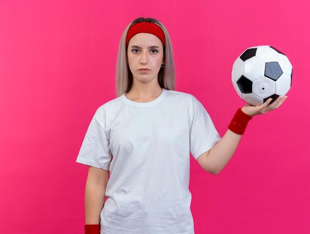 Fiduciosa giovane donna sportiva con bretelle che indossa fascia e braccialetti tiene palla isolata sulla parete rosa