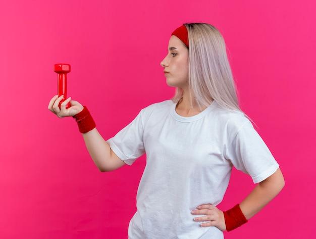 Fiduciosa giovane donna sportiva con le parentesi graffe che indossa la fascia e braccialetti tiene e guarda il manubrio isolato sulla parete rosa