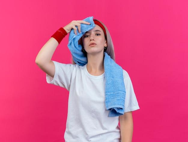 Fiduciosa giovane donna sportiva con bretelle che indossano fascia e braccialetti tiene e si asciuga la fronte con un asciugamano isolato sulla parete rosa