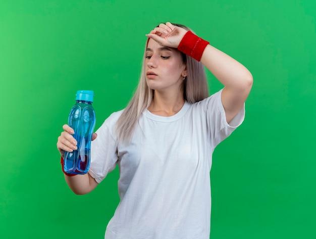 Fiduciosa giovane donna sportiva con bretelle che indossa fascia e braccialetti mette la mano sulla fronte e guarda la bottiglia d'acqua isolata sulla parete verde