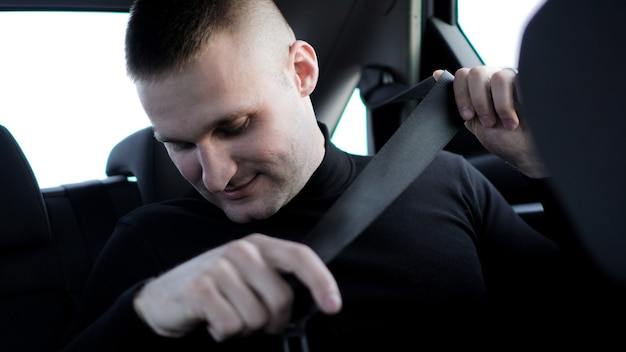 Confident young stylish businessman in his car fastening the seatbelt