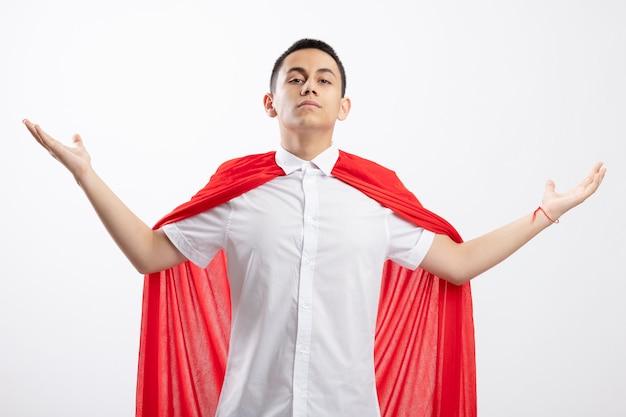 Уверенный молодой мальчик-супергерой в красном плаще смотрит в камеру, разводя руками, изолированными на белом фоне