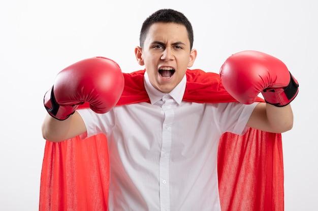 白い背景で隔離の叫び声で手を空中に保つカメラを見てボクシンググローブを身に着けている赤いマントの自信を持って若いスーパーヒーローの少年