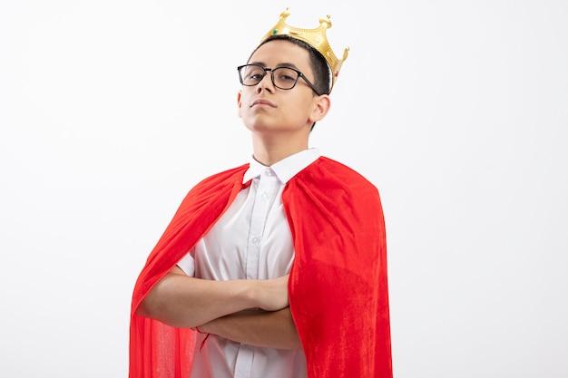 コピースペースと白い背景で隔離のカメラを見て閉じた姿勢で立っている眼鏡と王冠を身に着けている赤いマントの自信を持って若いスーパーヒーローの少年