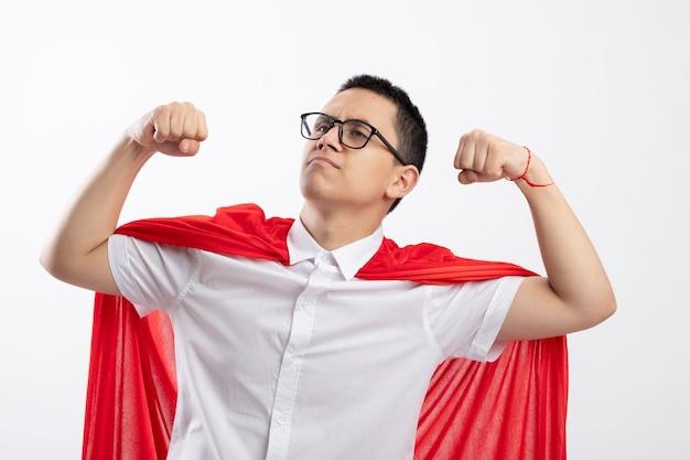 Уверенный молодой мальчик супергероя в красном плаще в очках делает сильный жест, глядя в сторону, изолированную на белом фоне