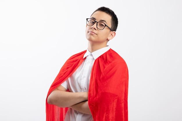 コピースペースと白い背景で隔離の縦断ビューで閉じた姿勢で立っている眼鏡をかけて赤いマントの自信を持って若いスーパーヒーローの少年