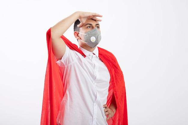 Уверенный молодой мальчик-супергерой в красной накидке в защитной маске, держащий руку на талии и на лбу, глядя прямо вдаль, изолированные на белом фоне с копией пространства