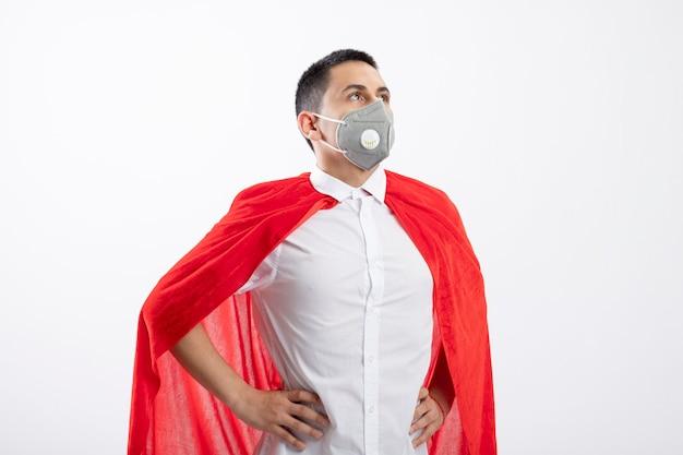 Уверенный молодой мальчик-супергерой в красной накидке в защитной маске, держа руки на талии, глядя вверх изолированно на белом фоне с копией пространства