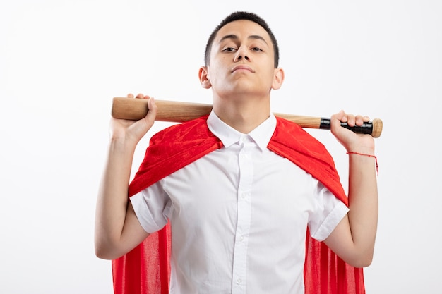 Confident young superhero boy in red cape holding baseball bat behind neck looking at camera isolated on white background