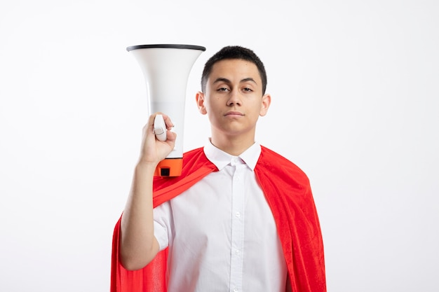 Confident young superhero boy in red cape holding speaker near head looking at camera isolated on white background with copy space