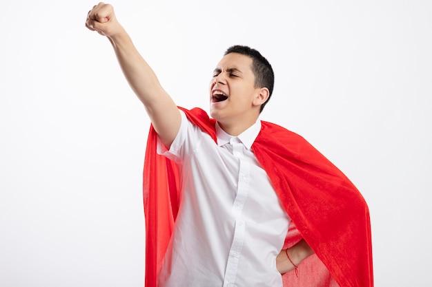 Fiducioso giovane supereroe ragazzo in mantello rosso tenendo la mano sulla vita guardando dritto alzando il pugno isolato su sfondo bianco con copia spazio