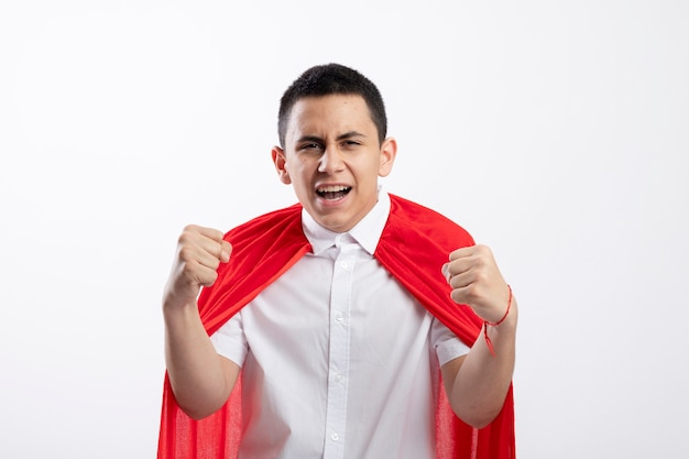 Confident young superhero boy in red cape looking at camera clenching fists isolated on white background with copy space