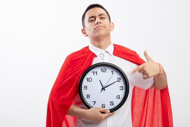Fiducioso giovane supereroe ragazzo in mantello rosso che guarda l'obbiettivo che tiene e che indica l'orologio isolato su priorità bassa bianca con lo spazio della copia