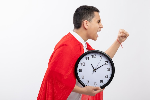 Fiducioso giovane supereroe ragazzo in mantello rosso in piedi in vista di profilo tenendo l'orologio alzando il pugno guardando dritto isolato su sfondo bianco con spazio di copia